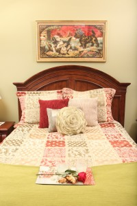 Beautiful bed, plush pillows, with a rose to complement the soothing decor